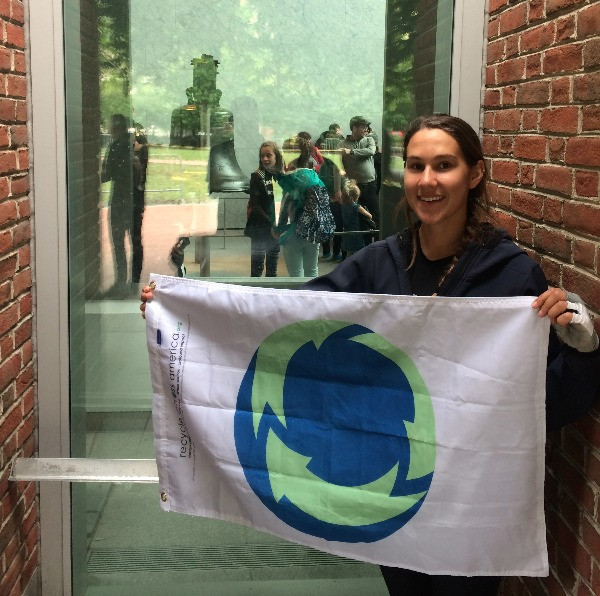 Maggie Sheerin poses with the RAA Earth Flag in front of the Liberty Bell