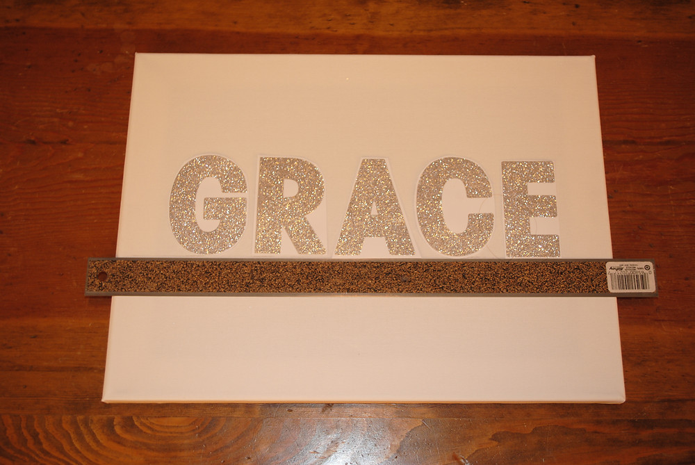 DIRECTIONS:  1) Initially, I just winged it and stuck the letters on. I kept having to remove it and reposition it. By the time I was done, the letters didn't stick anymore. Second time, I cut the letters out and placed them on the canvas on top of the ruler. This worked much better.
