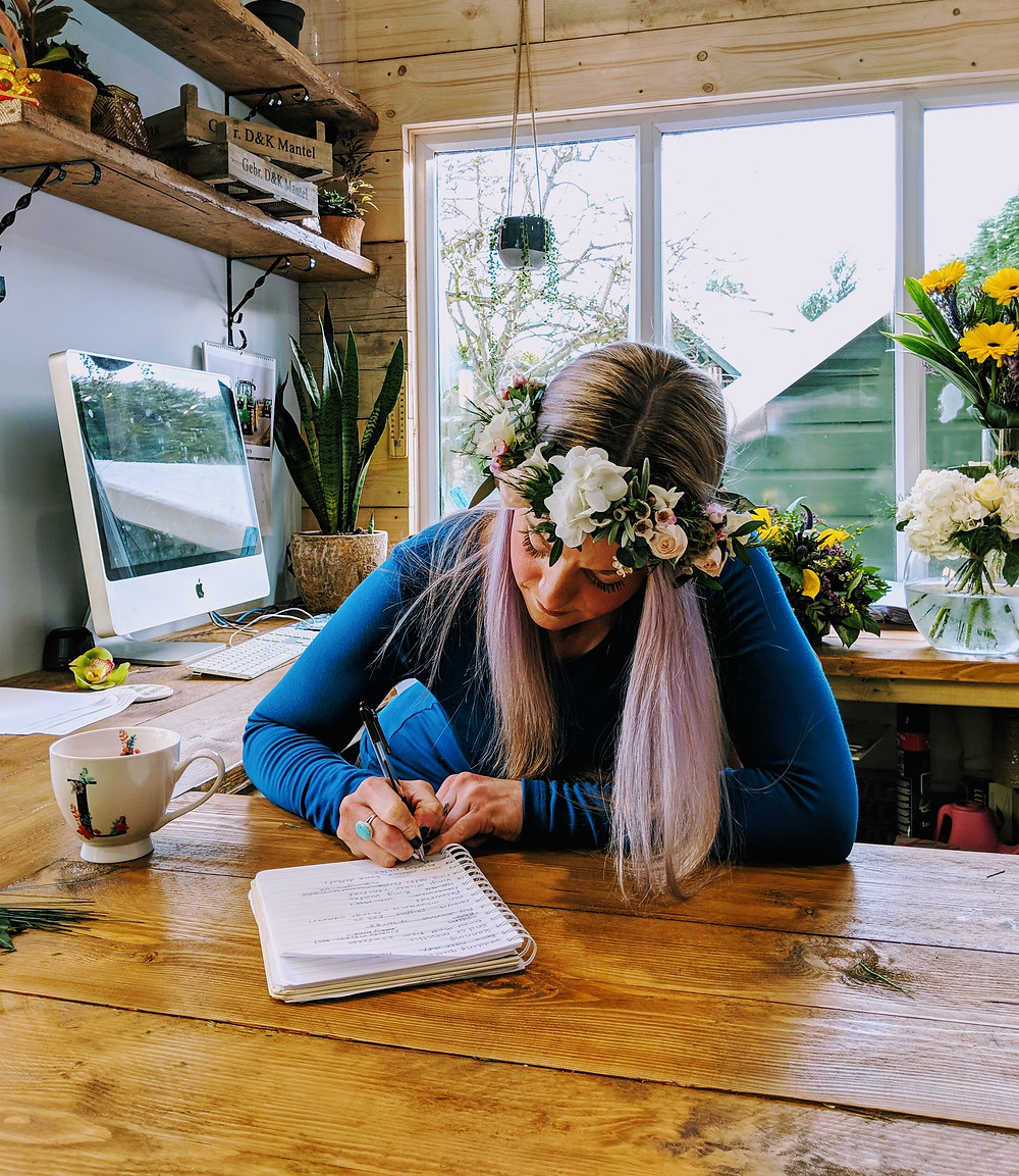Lady wearing floral crown and writing a list at the desk