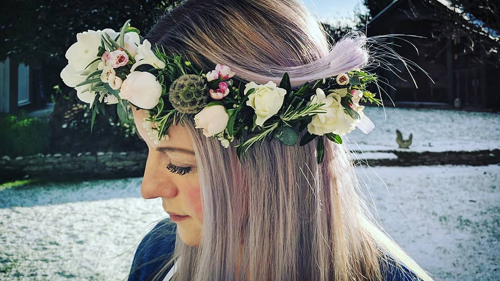 Lady with silver lilac hair wearing floral crown of spray roses, scabious & hydrangea.
