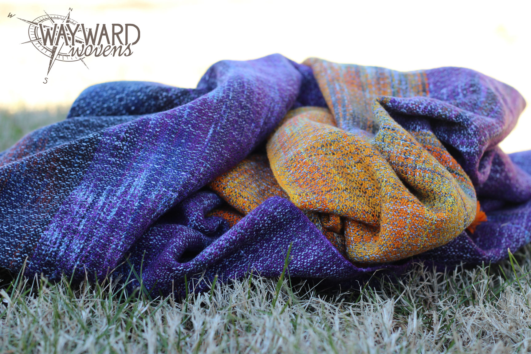 Woven wrap gathered in pile on grass