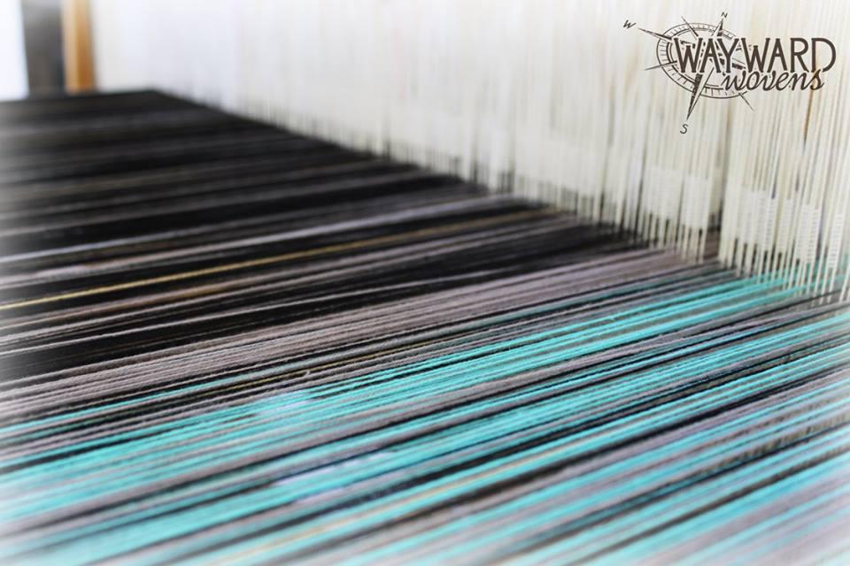 Warp threaded through heddles