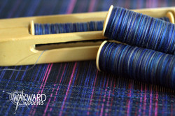 Woven cloth with shuttle and bobbins