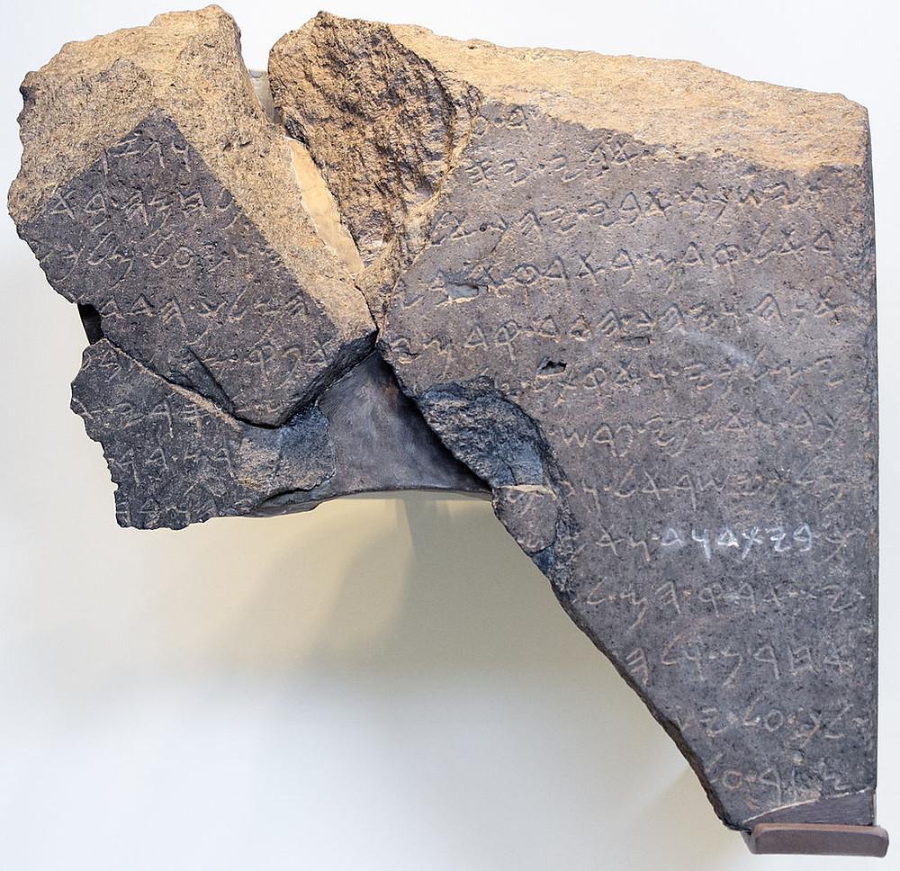 A foto mostra a Estela de Tel Dã em um fundo branco