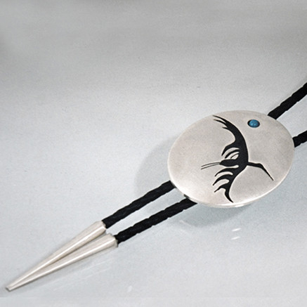 Bolo tie featuring the crane circling above Baawiting.
