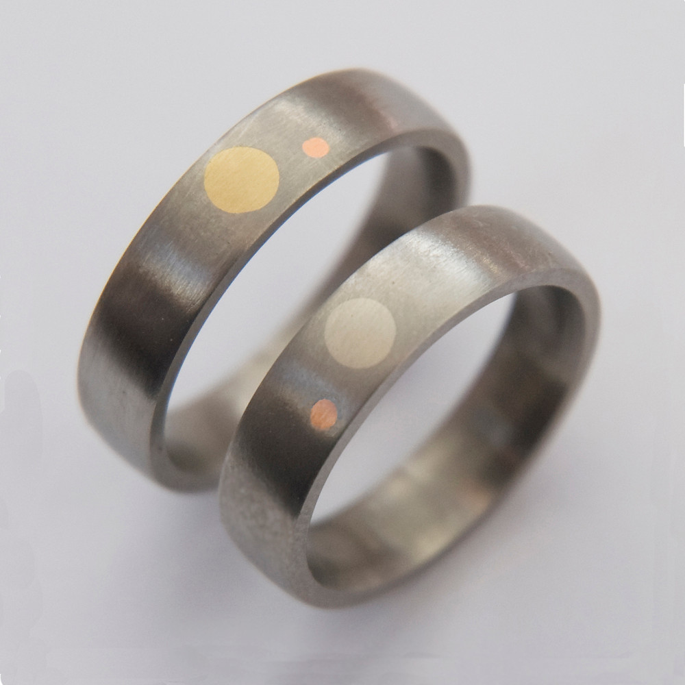 Zirconium wedding rings by Zhaawano Giizhik inlaid with yellow gold, white gold, and rose gold.