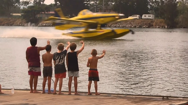 Kids waving at airtractor fireboss