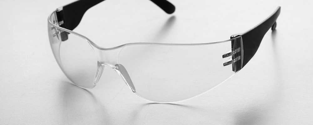 Protective goggles with black rod on white background.