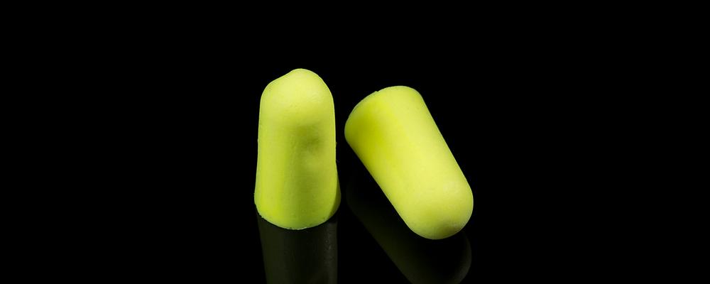 Tapones para los oídos amarillos sobre un fondo negro