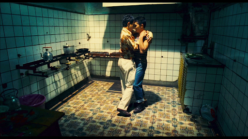 A still from Happy Together: Two men embrace, dancing in the kitchen, a spotlight is on them.