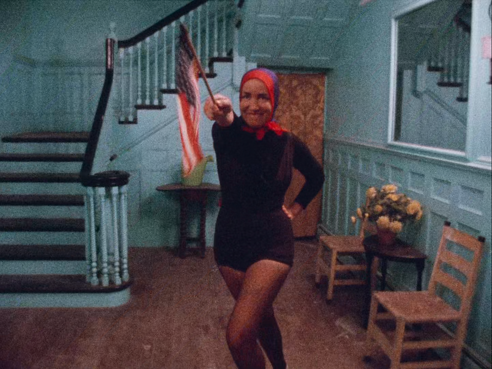 Little Edie from Grey Gardens in black leotard with red headscarf waving a small American flag while mid-dance