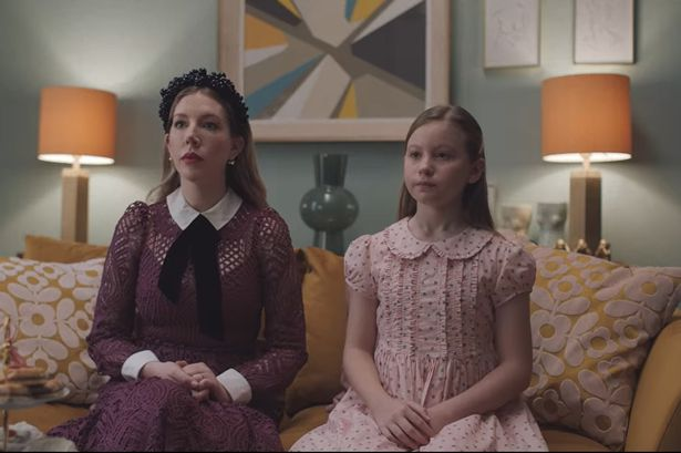 Katherine and her daughter sit on a sofa in a 'prim' fashion, wearing somewhat conservative outfits.