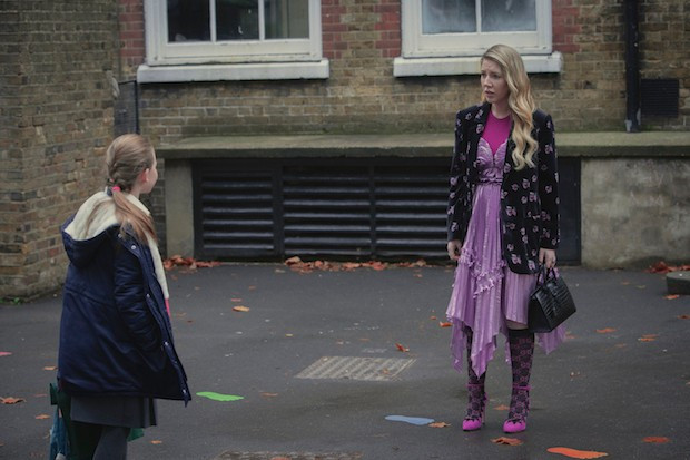Katherine and her daughter stand outside a plain building, looking like they are arguing. Katherine is wearing a lilac fairy-like dress, patterned tights and bright purple high heels.