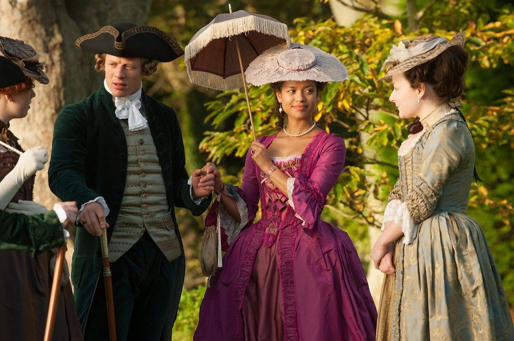 A still from Belle: four upper class people are standing in a garden, wearing opulent historical costume. Dido Belle holds a parasol and a man's hand. She is smiling gently at the woman next to her.