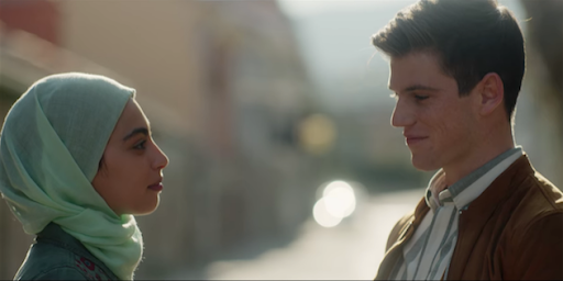 A still from Netflix's Elite: Nadia and Guzman are standing on a street facing each other, he is smiling at her