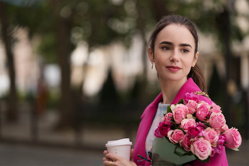 Emily, from Emily in Paris, stands on a blurred Parisian street, smiling gently and looking over her shoulder. She wears a bright pink blazer that matches the roses she is holding.