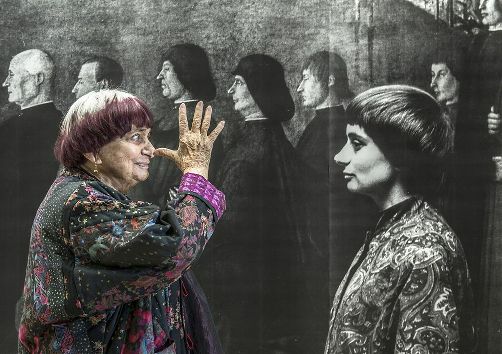Elderly Varda pulls a face at an image of the younger Varda, they are both in side profile but young Varda is in black and white, blending into an old painting of priests behind her. Varda is dressed in a colourful jacket.