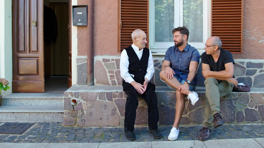 Zac Efron and two Italian men sit on a wall outside a typical Italian house