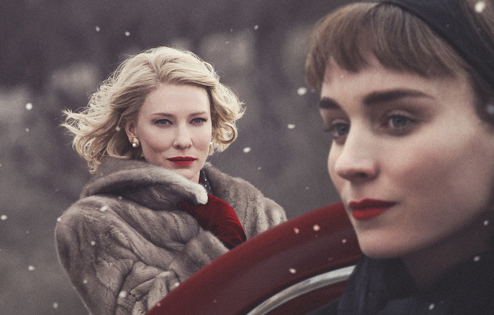 A still from Carol, a blonde woman is staring at a dark haired woman with a look of concentration from afar, the other woman looks off camera with a neutral expression. It is snowing