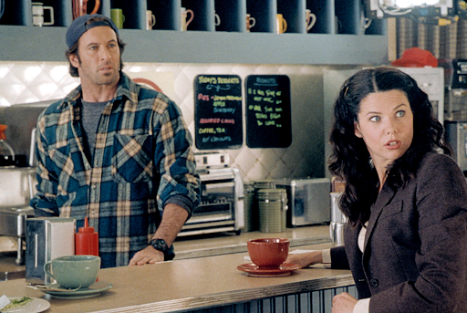 A still from Gilmore Girls:Luke Danes and Lorelai Gilmore in a coffee shop, turning around and looking surprised