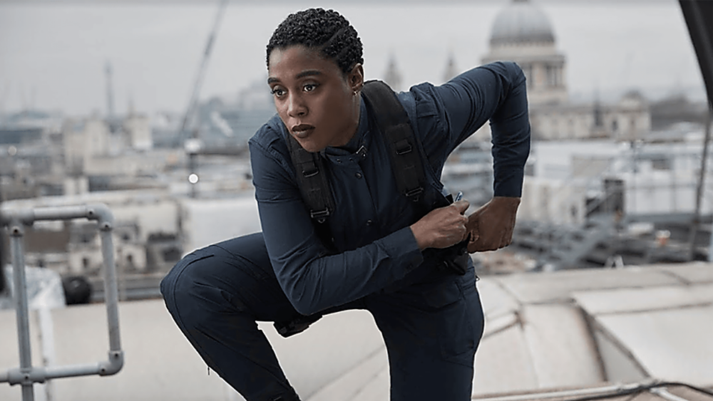 Lashana Lynch as Nomi in the new Bond film crouches on a roof over London, seeming to reach for a gun