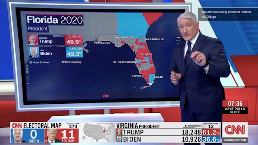 John King stands in the news room in front of a map of Florida, coloured in red and blue