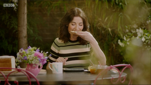 Nigella Lawson sits in a garden at a table eating a slice of bread.