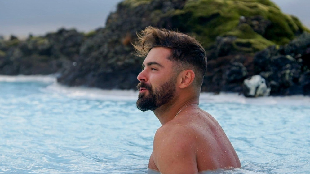Zac Efron is shirtless, half-submerged in a hot pool in Iceland