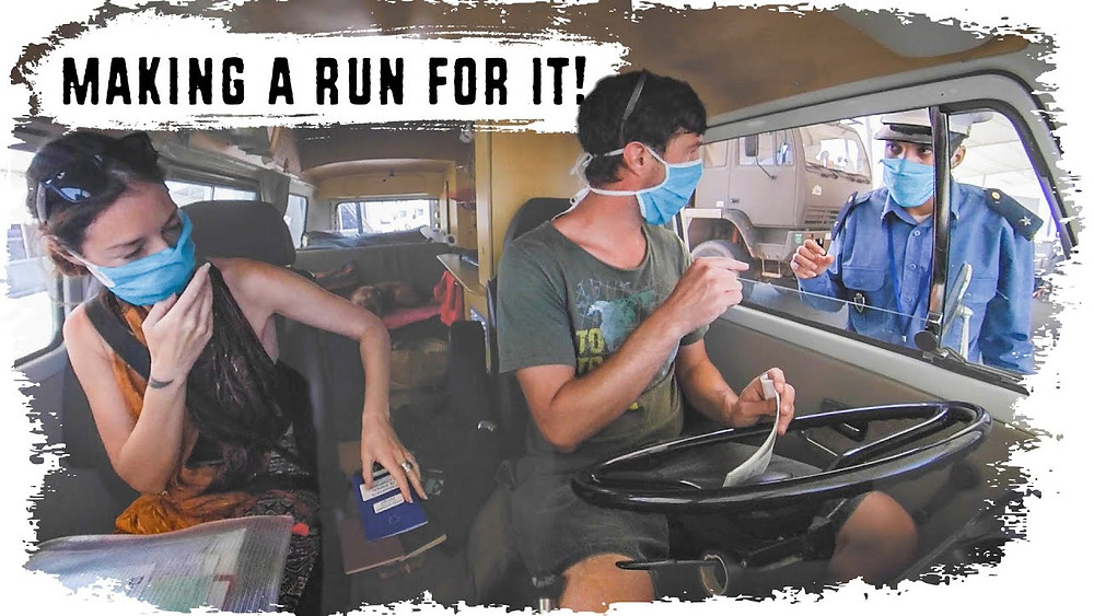Two vloggers are sat in a van with surgical masks on, pulled up to a checkpoint and passing documents to a guard dressed in uniform. The text reads 'Making a run for it!'