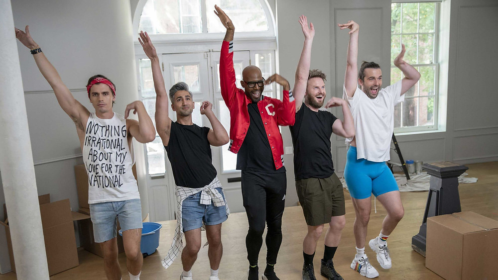 A still from Queer Eye, the five stylists all dance in a row with one hand up in the air and the other flicked towards them.