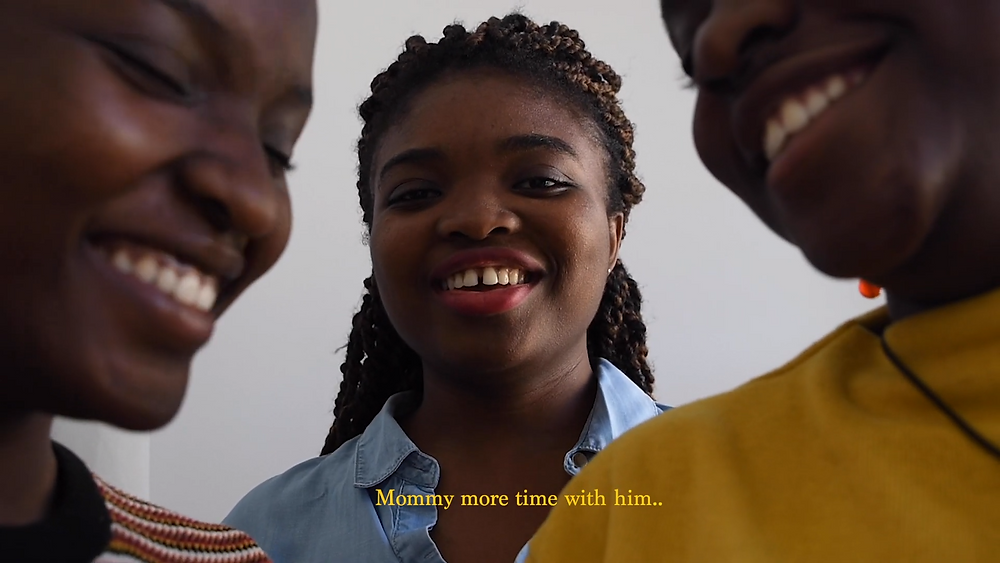 Three young Black women stand grouped, close to the camera with two in front, semi-obscured by the frame, and one behind in the middle: they are all laughing. The subtitles read 'Mommy more time with him...'