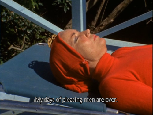 """middle aged woman in red polo wearing a red headscarf, lying down on a sun bed with eyes closed, saying """"My days of pleasing men are over"""