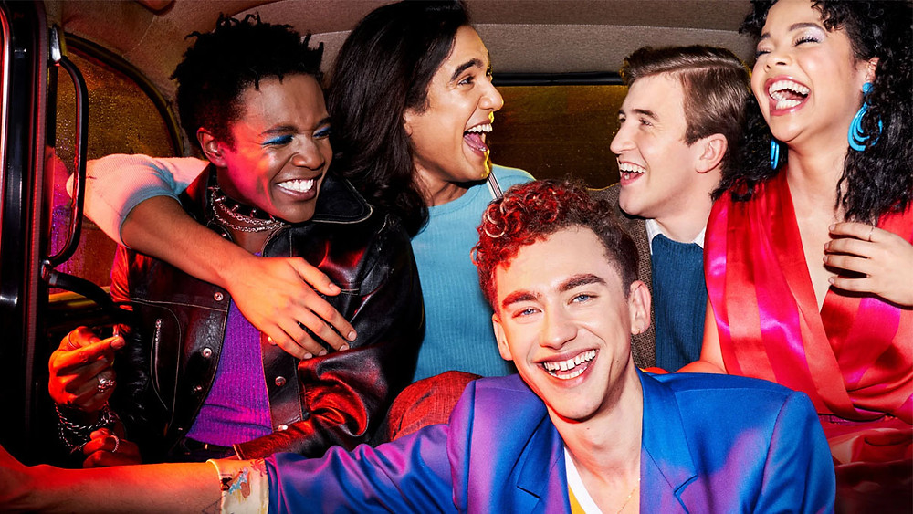 A still from It's a Sin, five friends is garish 80s outfits are laughing together, all embracing and smiling.