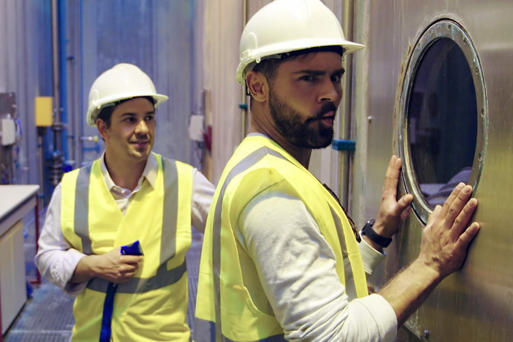 Zac Efron peers into the window of a water tank, wearing construction PPE, pulling a fish face