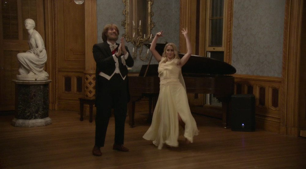 Borat, dressed in a disguise in full black tie, claps while his daughter dances in a yellow dress. They are in an ornate drawing room with a grand piano.