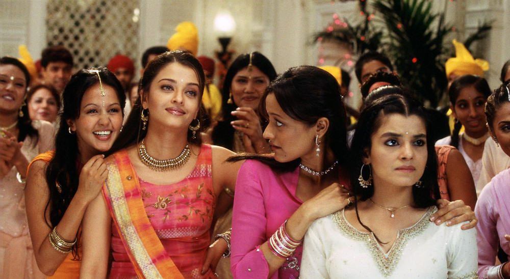 A wedding scene, four women stand in the foreground wearing saris and kameezes in shades of orange and pink