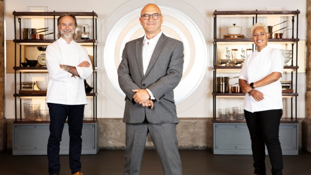 Greg Wallace, Marcus Wareing and Monica Galetti standing in formation with their arms crossed in front of shelves of kitchen utensils, and the Masterchef logo