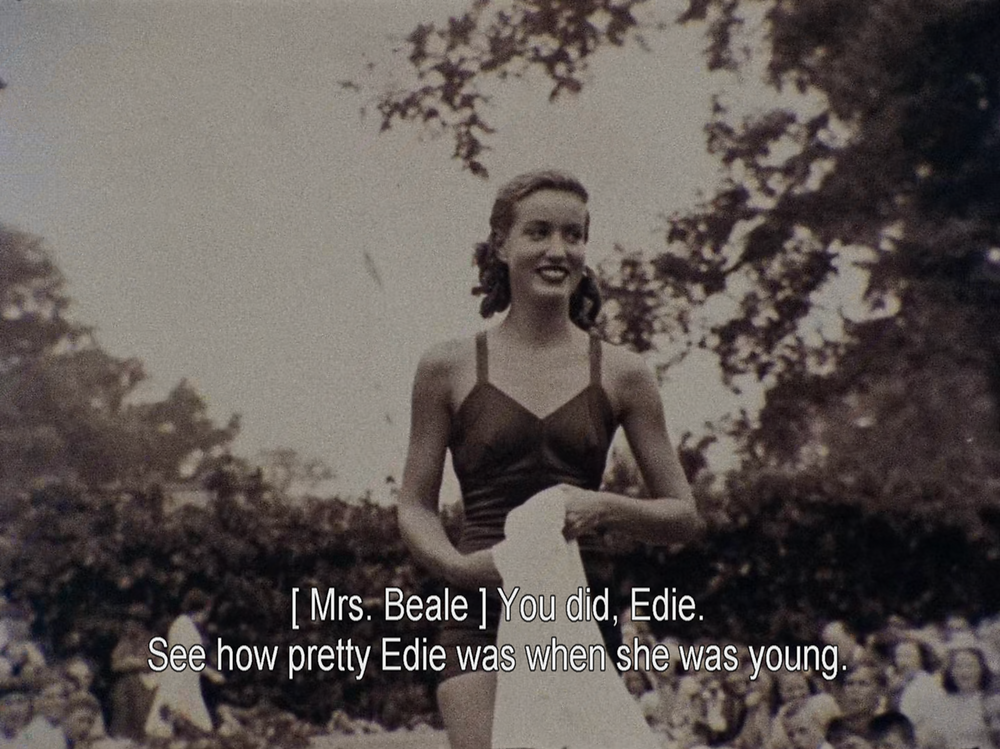 """a sepia picture of a young girl, smiling, dressed in a swimsuit carrying a towel. Subtitles are her mother saying """"See how pretty Edie was when she was young"""""""