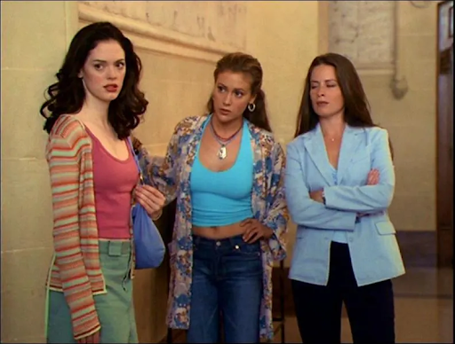 A still from Charmed: The trio are standing side-by-side in front of a plain background, looking towards something with a disappointed expression.