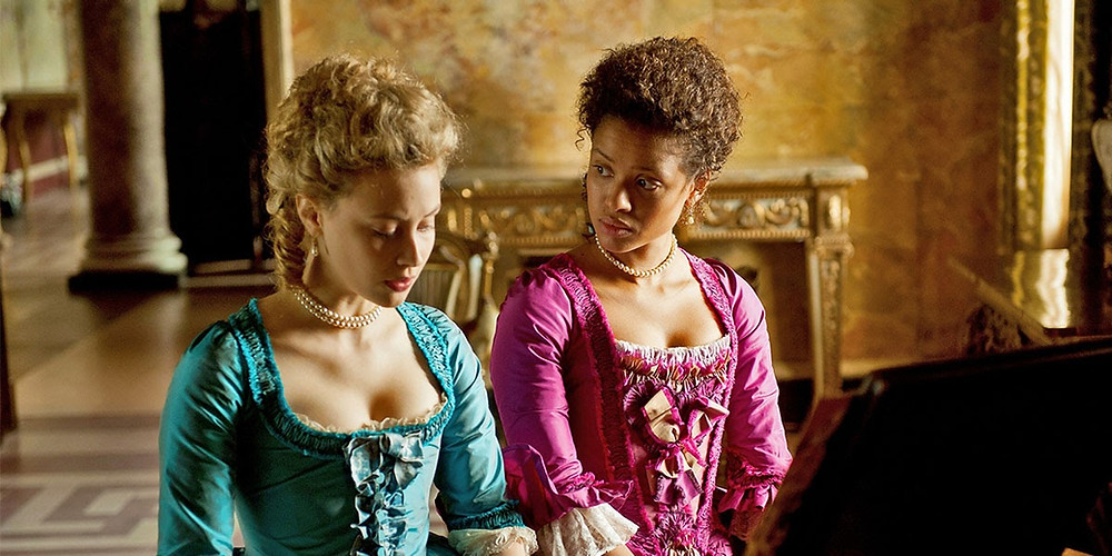 A still from Belle: Dido Belle and her step-sister sit at a piano, dressed in beautiful historical costumes, one turquoise one pink dress. Belle is looking at Elizabeth with concern.