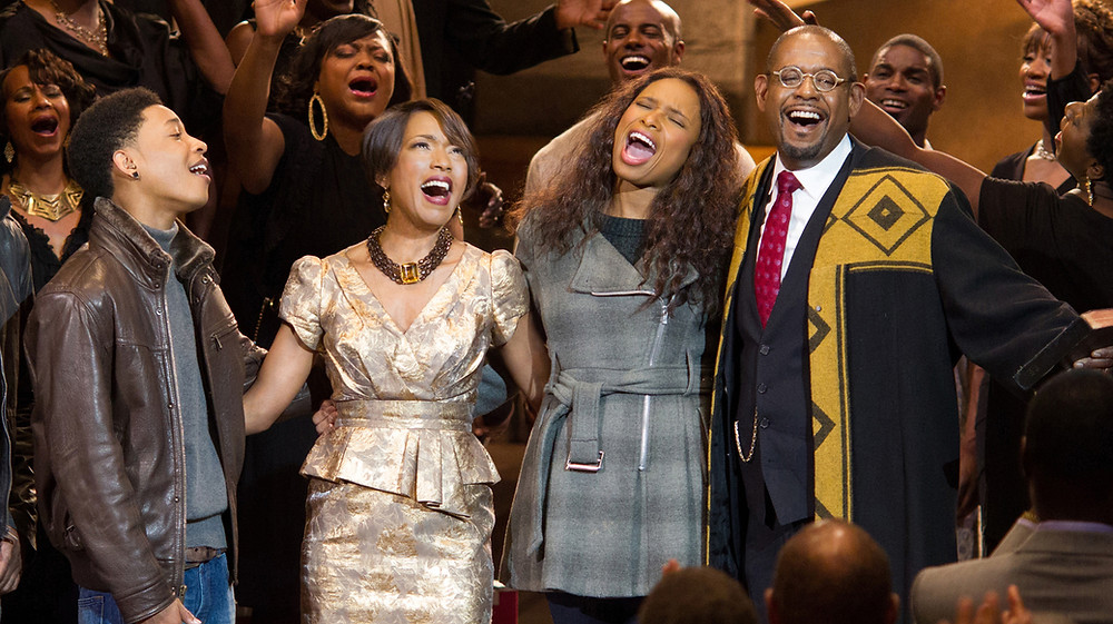 Four members of the cast of Black Nativity (including Jennifer Hudson) are singing in a gospel choir at the tops of their voices.