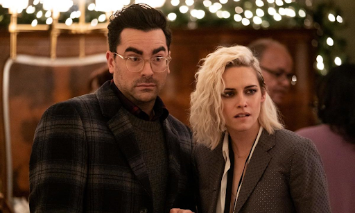 Kristen Stewart in Happiest Season, wearing a grey suit and Dan Levy in a tartan one, looking surprised/disgusted whilst looking at something in the distance