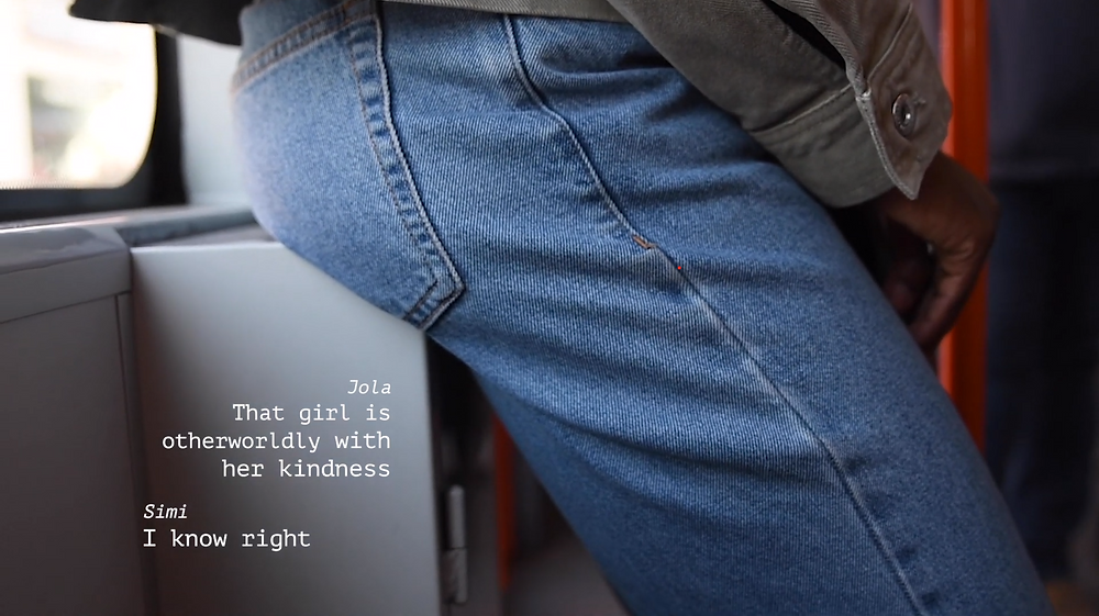 A close up of someone leaning against the side of a bus, only framed from the hips to the knees, wearing jeans. The subtitles appear like texts on screen, they read 'Jola: That girl is otherworldly with her kindness', 'Simi: I know right'