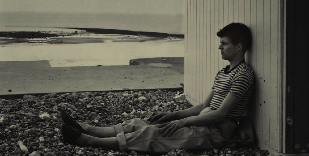 An old sepia photograph of Varda's friend Bourdin at the Normandy beach, sat on the ground with his legs out in front of him, leaning his back against a beach hut.