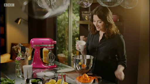 Nigella Lawson stands in her kitchen, smiling into the bowl of her hot pink kitchen aid whilst pouring cream in.