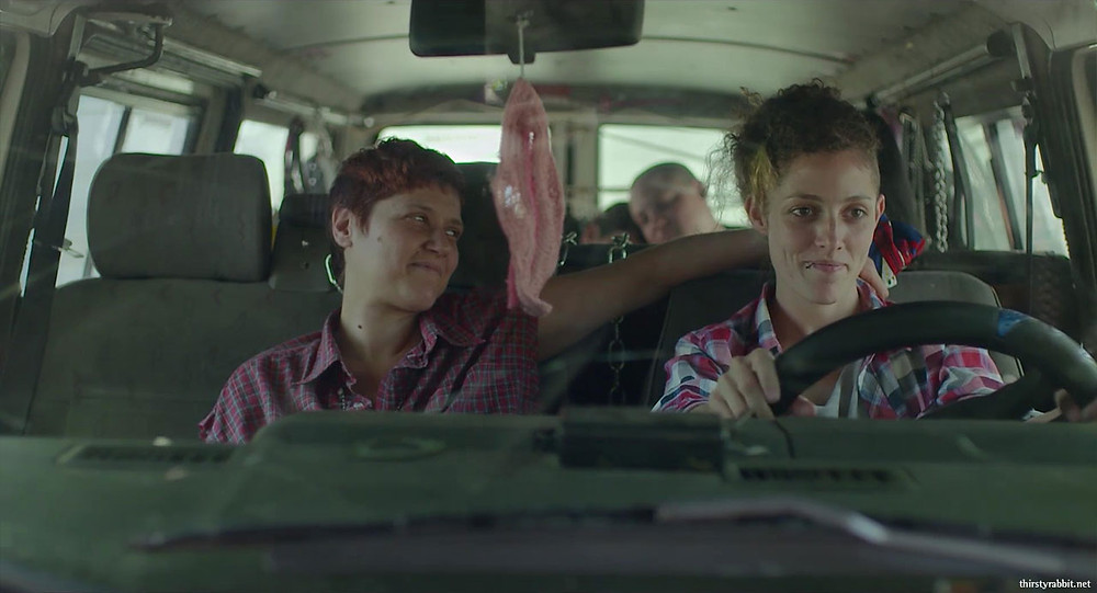 Two people sit next to eachother in a car, one is driving while the other looks at them affectionately. A vulva trinket hangs from the mirror.