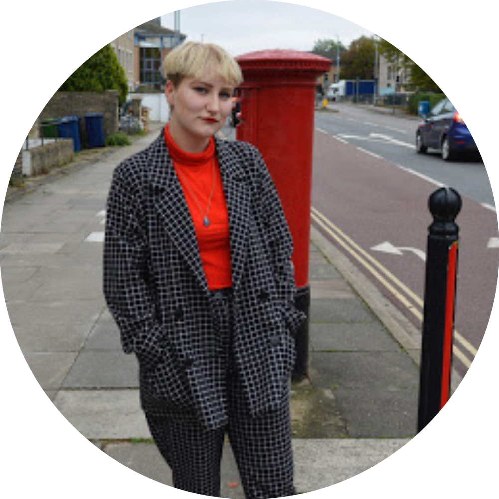 An image of Bea Godard in a red and black outfit, matching the red letterbox and pillar beside them