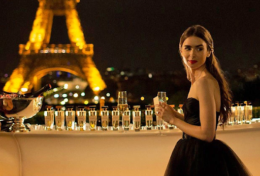 Emily is wearing a black ballgown, at an event in front of the Eiffel Tower at night, which glows yellow. She is standing in front of a table covered in Champagne glasses. She is alone, and smiles over her shoulder.