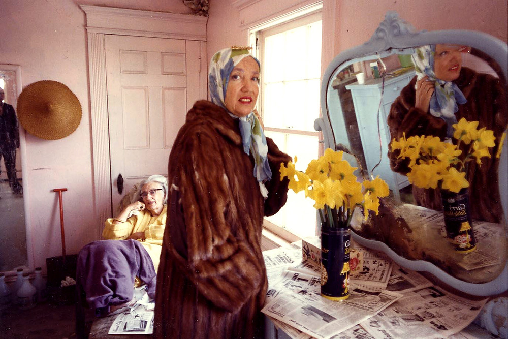 The Two Edie's from Green Gardens standing inside a white room. Middle-aged woman wearing red lipstick and long brown fur coat with a blue-and-white headscarf standing in the foreground, next to a cupboard with a bouquet of yellow flowers placed on top of it, over a pile of newspaper pages. Elderly woman sitting down in the background, wearing long yellow coat, with a purple blanket covering the bottom half of her body.
