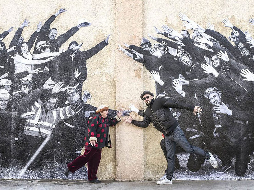 A still from Visages, Villages: JR and Varda pose as though they are running in front of a wall, where they have plastered the images of the workers waving their arms around.